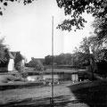 Hof Ganzow -  um 1920 | Blick vom Gutshaus über den Teich, links: Hafer- und Roggenscheune, mittig: Teich, Auffahrt und Toranlage, rechts: Weizen- und Gerstenscheune