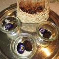 süß-sauer eingelegte walnüsse mit mohn-sahne-fichtenspitzen-spitzwegerich-creme und stiefmütterchenblüte - oben am bild sind kämpen - trennwände der walnüsse