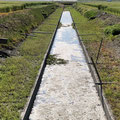 水が抜かれた状態のクリーク断面写真。中央に溝が走っていて、ココに着くライギョもいるため、岸沿いやストラクチャ―周りだけでなく、クリーク中央部も気を抜けない。