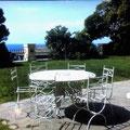 Tavolo in ghisa e sedie in ferro battuto con piano in marmo intarsiato.