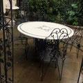 Tavolo e sedie in ferro battuto con piano in marmo intarsiato.