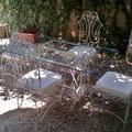 Tavolo e sedie in ferro battuto con piano in cristallo molato. Anni '60