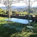 Tavolo e sedie in ferro battuto con piano in cristallo molato.