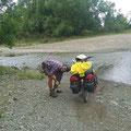 Wir wollen keine nassen Schuhe riskieren. Das Durchfahren der Furt mit den grossen Steinen ist mit den schweren Velos heikel.