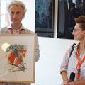 1. Preis der Publikumsverlosung: eine Monotypie des Künstlers Kyomu (links). Neben ihm die Kuratorin Menia.