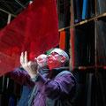 A. Linnenschmidt prüft Gläser für seine Arbeit