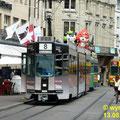 """Ein Gelenktriebwagen Be 4/6 mit Speziallackerung """"Basel-Tatoo"""" und einem Beiwagen am Marktplatz."""