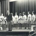 Piet Hopmans achter de microfoon op het podium samen met de Fatimo's