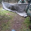 Aufbau des Verstecks: Ein Poncho wird als Regenschutz möglichst nah über dem Boden aufgespannt.