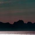 Im Gegenlicht erscheint die Lofotenwand am Horizont.