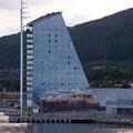 Bei der Abfahrt aus Molde spiegelt sich die MS Kong Harald in der Fassade des Rica Hotels.