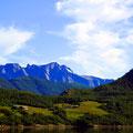 Über malerischem Grün türmen sich alpine Berge.