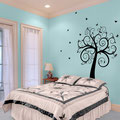 Black Curly Tree vinyl wall art sticker with butterflies in a bedroom.