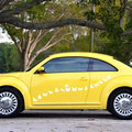A yellow car with white butterfly decals across the door.