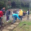 側溝のふたを掘り出し、ふたを上げ泥をかき出す