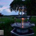 Edelstahlbrunnen -  Gartenbrunnen aus Edelstahl mit Efeuranken auf Granitsäule - LED-Beleuchtung in der Dämmerung (© Raven Metall Design)