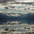 Unter dem schmalen Landstrich spiegeln sich die Wolken im Sell