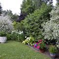 Liebevoll gepflegter Garten mit viel Grün ringsherum.