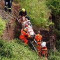 An einer Stützmauer wird eine Leiter als Gleitbahn zu HIlfe genommen.