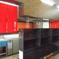 テーブル席から厨房を見る.キープ棚と印象的な赤いのれん.