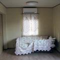 内観.入口からベッドを見る.やわらかい色使いとしました.