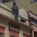 Und diese gruenen Figuren, die ueberall auf den Daechern der Stadt sitzen, hat ebenfalls ein Kunstler erstellt.