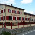 Eine große Terrasse in den Bergen mit farblich dem Haus angepasster Windschutzanlage