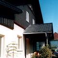 Gartenansicht mit sanierter Fassade und teilweise überdachter Terrasse