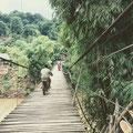 Hängebrücke aus Stahlseilen und Holzbrettern – trägt Mopeds und Fußgänger