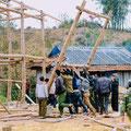 Ein Holz-Haus auf Stelzen, ein Nha San wird von den Männern des Dorfes errichtet.