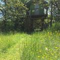 Das Baumhaus für die Kinder, darunter Sitzgruppe oder Übernachtungsmöglichkeit bei Regen auf Feldbetten