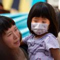 Kind mit Mundschutz hat eine Schilddrüsenerkrankung.