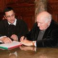 Hubert Yonnet signe le renouvellement de l'acte fondateur de la Confrérie sous le regard de Maître Jean-Pierre Gilles en costume d'époque