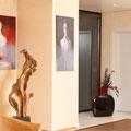 Surrealistische Kunst und Bronzeskulptur im Eingangsbereich der Kunstagentur Bild und Raum