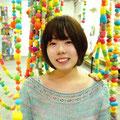 いつも笑顔の高津戸優子さん。カラフルな作品の色は高津戸さんの雰囲気にぴったり。