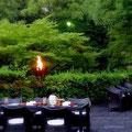 篝火が焚かれ、テーブルがセッティングされた、緑滴る太閤園のお庭です。
