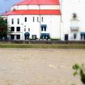 宝塚大劇場と、その前を流れる大雨で水かさが増えた武庫川の濁流。