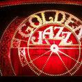 宝塚月組公演「GOLDEN JAZZ」の開演前の舞台です。赤を基調にした電飾の中に「GOLDEN JAZZ」の文字がくっきりと浮かんでいます。