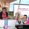 Marion Tischler mit Kunst S:nack im Holzkiosk und Dreirad