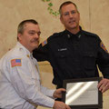 Assistant Chief Zawodniak presents Firefighter Gorman with a K of C Shield award