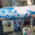 Tatouage bleu fleurs oiseau