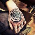 Tatouage d'une fleur noire sur la main