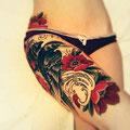 Tatouage d'un oiseau et de fleurs sur la cuisse