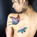 Tatouages de papillons colorés sur l'épaule