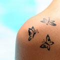 Petits tatouages de papillons sur l'épaule