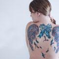 Tatouage ailes et noeud cadeau dos