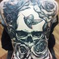 Tatouage d'une tête de mort, d'un papillon de nuit et de roses noires