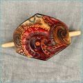 Lederhaarspange, rautenförmig mit Buchenholzstab als Verschluss, punziertes Paisleymuster in Rot- und Brauntönen, mittelgroß