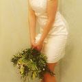 Kurzes, sommerliches Brautkleid aus elfenbeinfarbenem, mattglänzendem Satin aus kühler Seiden-Baumwollmischung mit aufwendig mit Blumen besticktem Seiden-Organza am Ausschnitt. Vorne hochgeschlossen und hinten mit kleinem V-Ausschnitt, den Körper dezent u