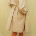 Wintermantel aus hochwertigster Schurwolle mit grau-beigem, dezenten Mini-Karo-Muster aufwendiger Schnitt, tiefe Falten am Schoß mit versteckten Taschen, Reißverschluss und verdeckte Druckknöpfe vorne. Im Nacken hoher Stehkragen